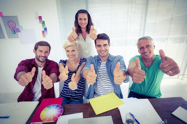 Szczęśliwa kreatywnie biznes drużyna gestykuluje aprobaty