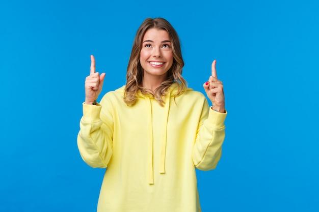 Szczęśliwa kusząca kaukaska kobieta o blond włosach w żółtej bluzie z kapturem, szukająca możliwości kariery, znalazła coś interesującego, patrząc i wskazując palcami w górę, uśmiechnięta zadowolona