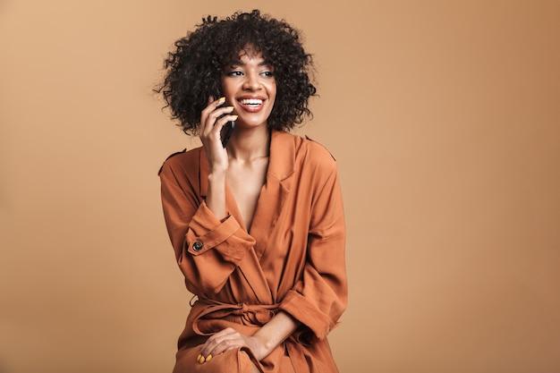 Szczęśliwa ładna afrykańska kobieta rozmawiająca przez smartfona i odwracająca wzrok na brązowym tle