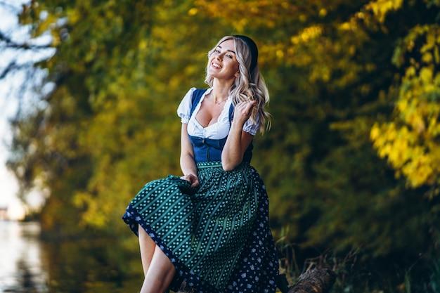 Szczęśliwa ładna blond dziewczyna w dirndl, tradycyjny strój festiwalu piwa, siedząc na zewnątrz z blured kolorowych drzew w tyle