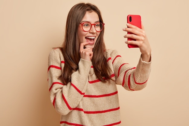 Szczęśliwa ładna dziewczyna robi śmieszne fotki, klika zdjęcie selfie na nowoczesnym telefonie komórkowym, publikuje posty w sieci społecznościowej, lubi się fotografować, nosi przezroczyste okulary, nosi swobodny sweter, izolowana