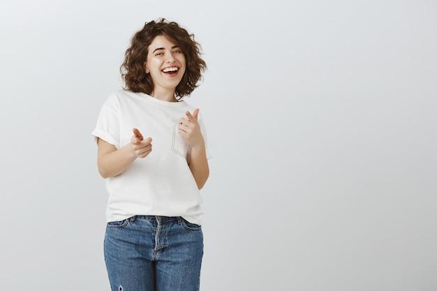 Szczęśliwa ładna dziewczyna wskazując palcami, dobra robota, dobra robota, gest gratulacje
