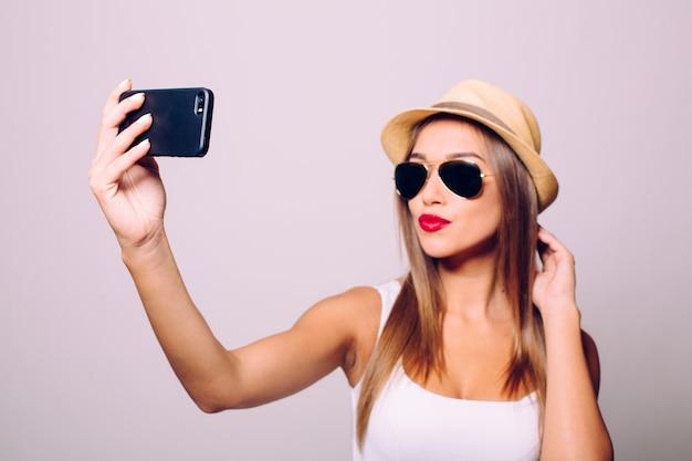 Szczęśliwa ładna kobieta dokonywanie selfie na białym tle nad szarą ścianą.