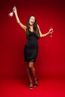 Szczęśliwa ładna kobieta korzystających ze strony, trzymając butelkę szampana i kieliszek, na białym tle na czerwonej ścianie