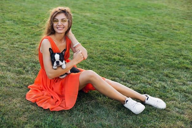 Szczęśliwa ładna kobieta siedzi na trawie w letnim parku, trzymając psa boston terrier, uśmiechnięty pozytywny nastrój, ubrana w pomarańczową sukienkę, modny styl, szczupłe nogi, trampki, zabawa ze zwierzakiem
