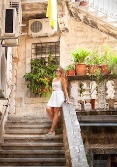 Szczęśliwa ładna kobieta stojąca na kamiennych schodach na podwórku w słoneczny dzień
