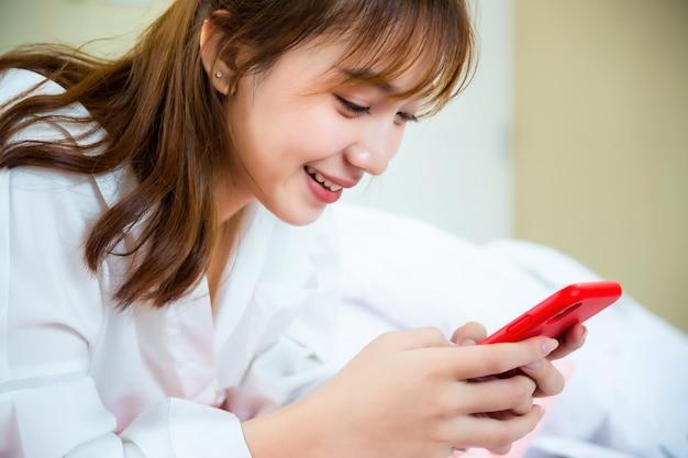 Szczęśliwa ładna kobieta używa smartphone na łóżku