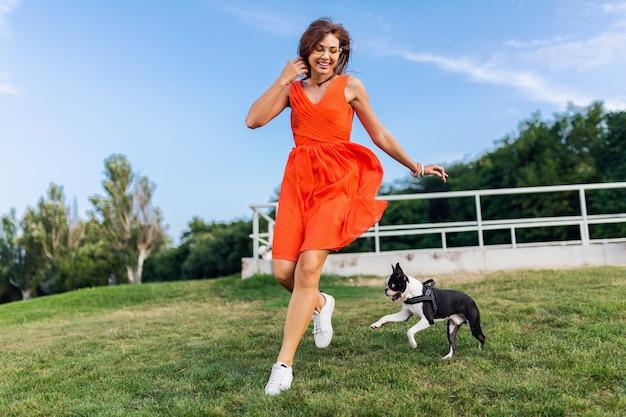 Szczęśliwa ładna kobieta w parku biegnie z psem boston terrier, uśmiechnięty pozytywny nastrój, modny letni styl, ubrana w pomarańczową sukienkę, bawi się ze zwierzakiem, dobra zabawa, kolorowe, aktywne wakacje weekendowe, trampki
