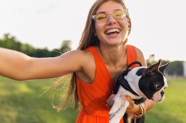 Szczęśliwa ładna kobieta w parku robi selfie zdjęcie, trzyma boston terrier, uśmiechnięty pozytywny nastrój, modny letni styl, na sobie pomarańczową sukienkę, okulary przeciwsłoneczne, zabawa ze zwierzakiem, zabawa