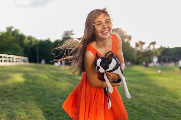 Szczęśliwa ładna kobieta w parku trzyma boston terrier psa, uśmiechnięty pozytywny nastrój, modny letni styl, ubrana w pomarańczową sukienkę, okulary przeciwsłoneczne, zabawa ze zwierzakiem, zabawa, słoneczna weekendowa rozrywka