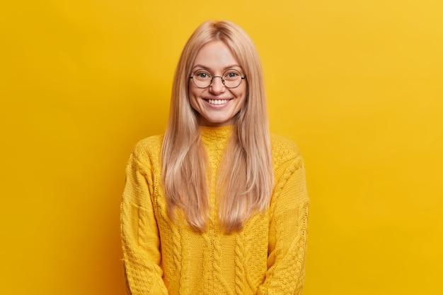 Szczęśliwa ładna kobieta z radosnym wyrazem twarzy uśmiecha się delikatnie czuje się usatysfakcjonowana pokazuje białe idealne zęby ubrane w swobodny sweter słucha ciekawych historii lub dobrych wiadomości