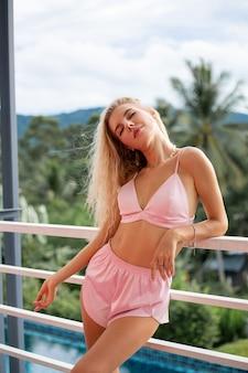 Szczęśliwa ładna młoda blondynka z kręconymi włosami w czasie snu nosić bieliznę, jasnoróżowy biustonosz i szorty