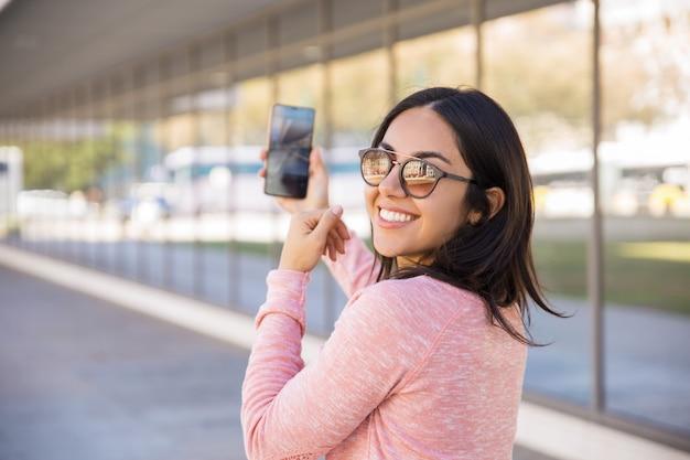 Szczęśliwa ładna młoda dama bierze selfie fotografię outdoors