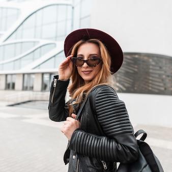 Szczęśliwa ładna młoda hipster kobieta w stylowy fioletowy kapelusz w modnych okularach przeciwsłonecznych w czarnej kurtce vintage ze skórzanym plecakiem