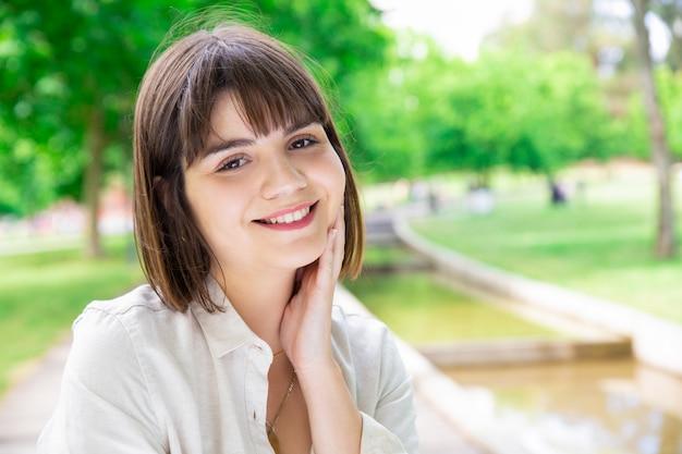 Szczęśliwa ładna młoda kobieta cieszy się naturę w miasto parku