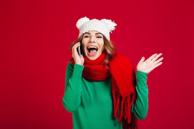 Szczęśliwa ładna młoda kobieta opowiada telefonem.
