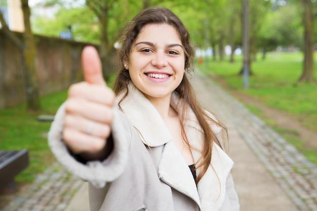 Szczęśliwa ładna młoda kobieta pokazuje kciuk up w parku