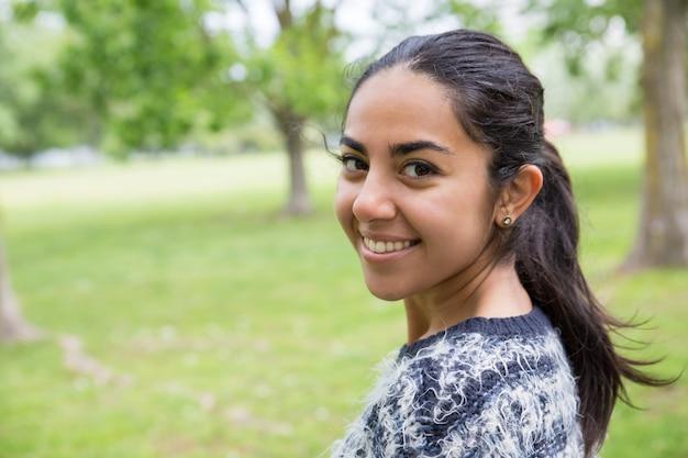 Szczęśliwa ładna młoda kobieta pozuje przy kamerą w parku