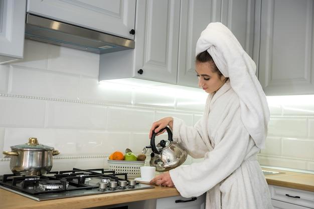 Szczęśliwa ładna młoda kobieta przed dniem roboczym cieszy się kawą w kuchni po prysznic w szlafroku. sam w domu, kwarantanna