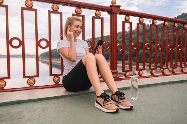 Szczęśliwa ładna młoda kobieta przygotowuje się do biegania i siedzi na ulicy podczas korzystania z telefonu komórkowego i patrząc na ekran