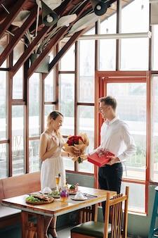 Szczęśliwa ładna młoda kobieta, przyjmując bukiet kwiatów i prezent od chłopaka