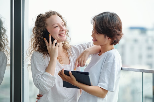Szczęśliwa ładna młoda kobieta rozmawia przez telefon, stojąc obok swojej dziewczyny z cyfrowym tabletem