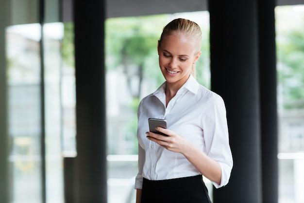 Szczęśliwa ładna młoda kobieta stojąca i korzystająca z telefonu komórkowego na zewnątrz