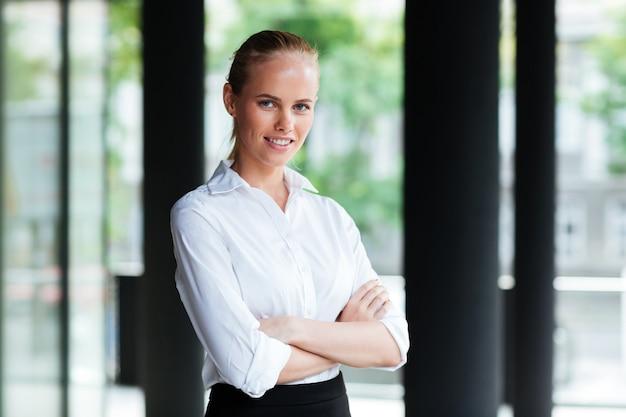 Szczęśliwa ładna młoda kobieta stojąca z rękami skrzyżowanymi na zewnątrz