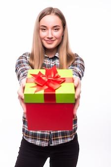 Szczęśliwa ładna młoda kobieta trzyma pudełko na białej ścianie