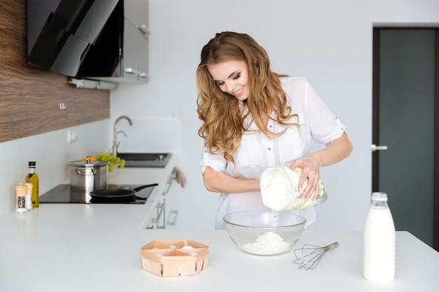 Szczęśliwa ładna młoda kobieta w białym gównie stojąca i gotująca w kuchni