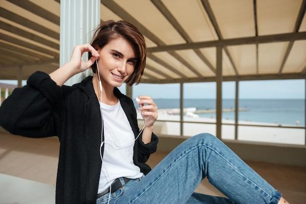 Szczęśliwa ładna młoda kobieta w słuchawkach siedzi i słuchanie muzyki na tarasie nad morzem