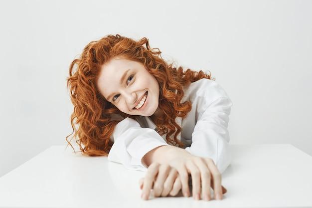 Szczęśliwa ładna młoda kobieta z rude włosy, uśmiechając się, patrząc na kamery, siedząc przy stole na białej ścianie