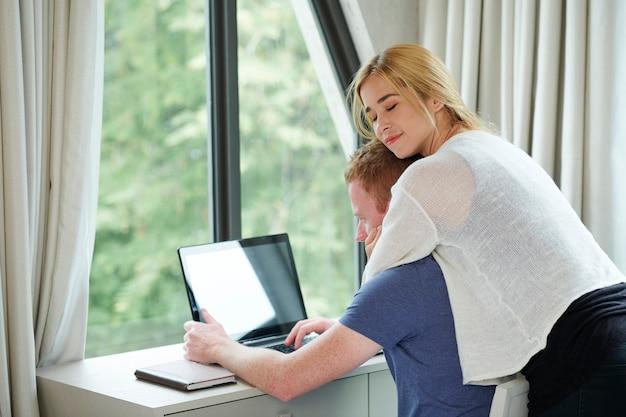Szczęśliwa ładna młoda kobieta zamyka oczy, gdy przytula swojego chłopaka pracującego na laptopie w domu z powodu pandemii koronawirusa