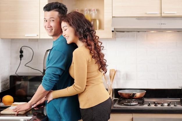 Szczęśliwa ładna młoda uśmiechnięta wietnamska kobieta przytulająca chłopaka gotującego śniadanie przy kuchennym blacie