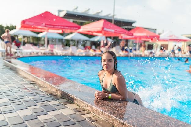 Szczęśliwa ładna nastolatka wyszła z basenu z czystą, błękitną wodą w słoneczny ciepły letni dzień w hotelu podczas wakacji