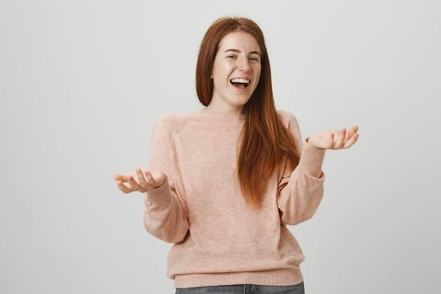 Szczęśliwa ładna ruda kobieta śmieje się, oglądając komedię
