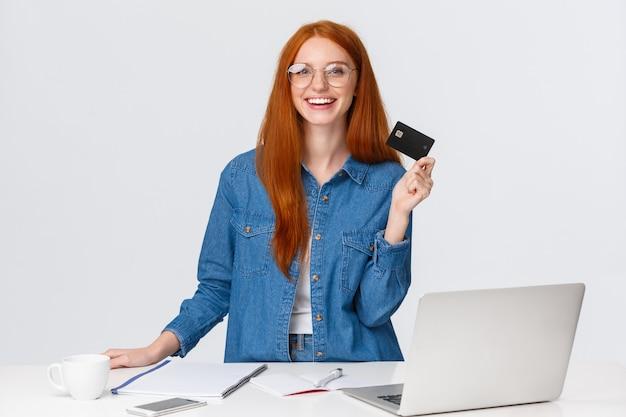 Szczęśliwa, ładna studentka zamówiła dostawę sztuki online ból, stojący w pobliżu biurka i laptopa, śmiejąc się i uśmiechając radośnie, pokazując kartę kredytową, zakupy w internecie, biały