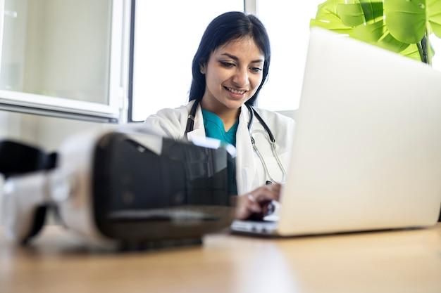 Szczęśliwa lekarka w swoim biurze przy użyciu komputera i okularów wirtualnej rzeczywistości