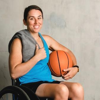 Szczęśliwa lekkoatletka na wózku inwalidzkim z piłką do koszykówki
