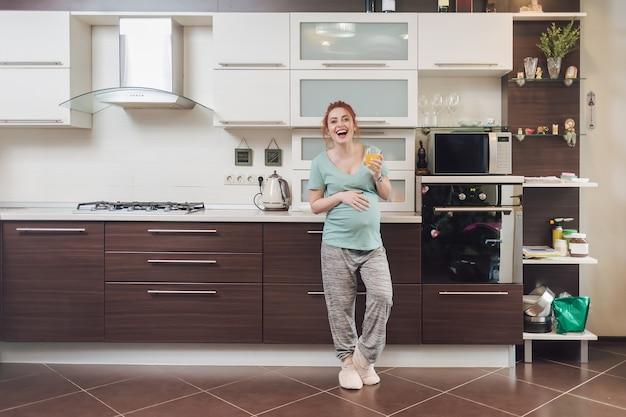 Szczęśliwa loughing pregnat kobieta w kuchni.