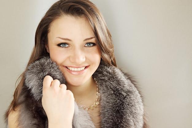 Szczęśliwa luksusowa brunetka w futrzanej pelerynie