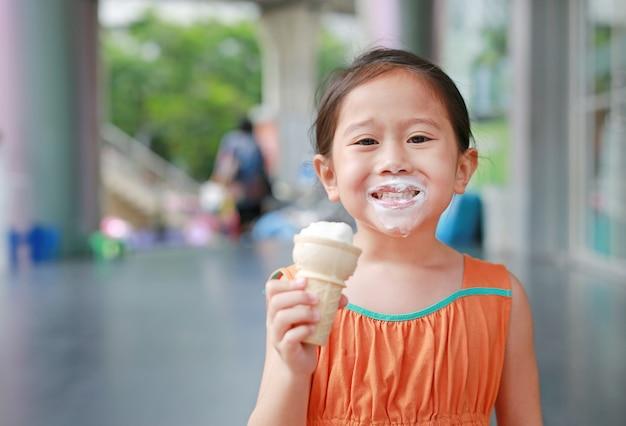 Szczęśliwa mała azjatycka dzieciak dziewczyna cieszy się łasowanie lody z poplamionym wokoło jej usta.