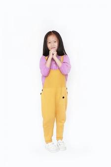Szczęśliwa mała azjatycka dziecko dziewczyna w dungarees wyrażeniowych rękach błaga odosobnionego.
