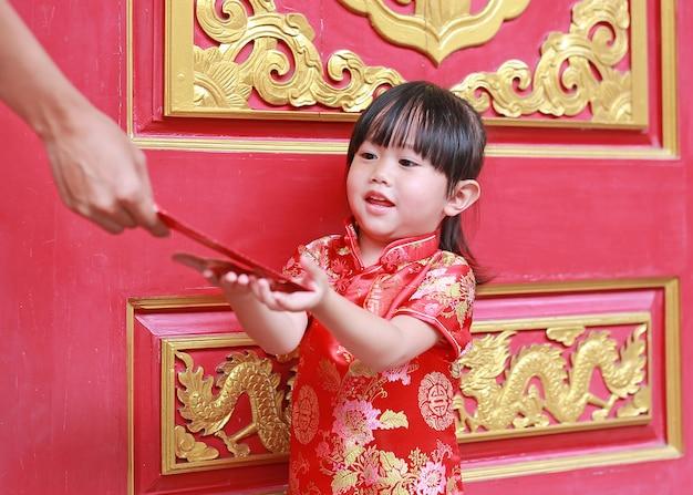 Szczęśliwa mała azjatycka dziewczyna otrzymywał czerwoną kopertę. obchody chińskiego nowego roku.