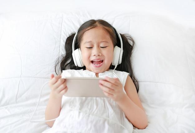 Szczęśliwa mała azjatycka dziewczyna używa hełmofony słucha muzykę