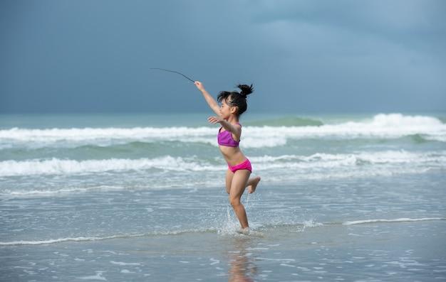 Szczęśliwa mała azjatycka dziewczyna z jej biegiem na plaży. zrelaksować się na wakacjach na świeżym powietrzu w tajlandii.