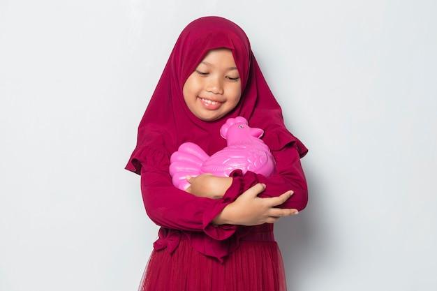 Szczęśliwa mała azjatycka muzułmańska dziewczyna oszczędzająca pieniądze z bankiem kurczaków na białym tle