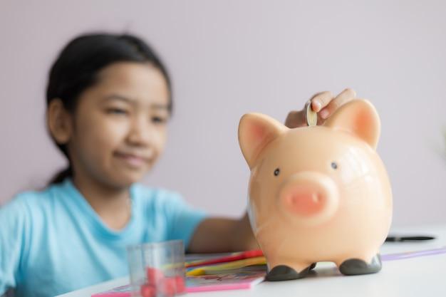 Szczęśliwa mała azjatykcia dziewczyny kładzenia pieniądze moneta w prosiątko banka