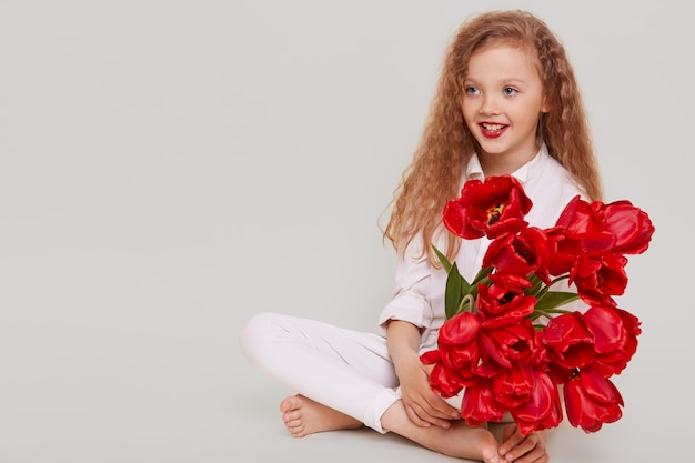 Szczęśliwa mała blondynka patrząc z uśmiechem toothy i pozytywnym wyrazem twarzy, siedząc na podłodze, trzymając bukiet czerwonych tulipanów