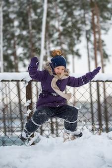 Szczęśliwa mała blondynka skoki w śniegu, dziecko zabawy grając ze śniegiem w zimowy dzień